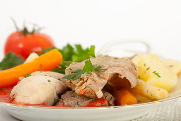 Boiled beef and chicken meat with creamy tomato sauce served with potatoes, carrots and dill