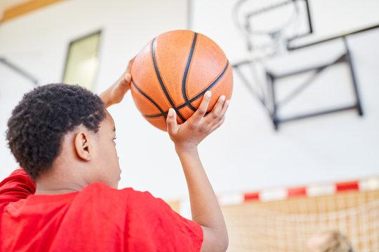 Junge mit dem Basketball in der Hand
