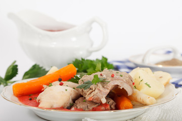 Boiled beef and chicken meat with creamy tomato sauce served with vegetables