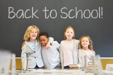 Schüler vor Tafel mit Back to School Slogan