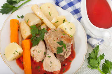 Boiled beef and chicken meat with creamy tomato sauce served with vegetables on white plate, top view