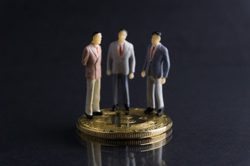 Bitcoin and businessman's miniature on dark background with selective focus and crop fragment