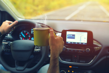Male driver drinking hot coffee while driving on road in autumn warm colors