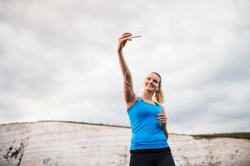 Young sporty woman runner with earphones and smartphone on the beach, taking selfie.