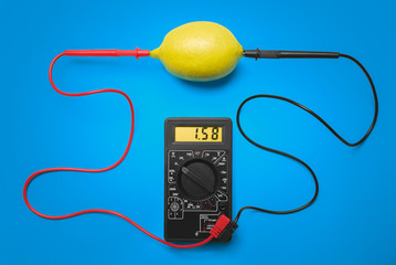 Measurement of electric tension in lemon. Blue background