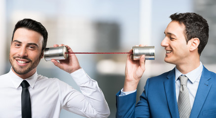 Men talking on tin can phone
