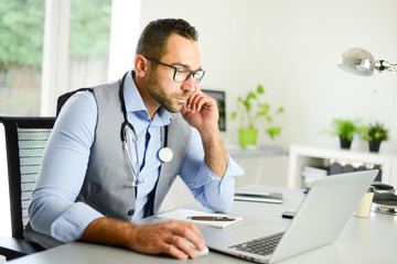 portrait of handsome man male doctor in medical practice office writing prescription in laptop computer