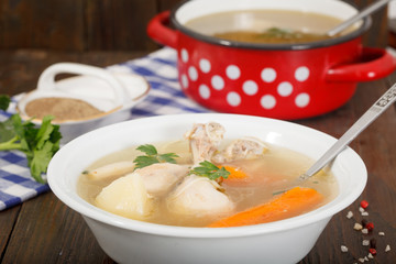 Hot homemade chicken soup in white bowl - alternative remedy for cold and flu. Red pot with soup in background on wooden table.