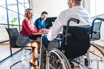 partial view of smiling businesspeople looking at colleague in wheelchair in office