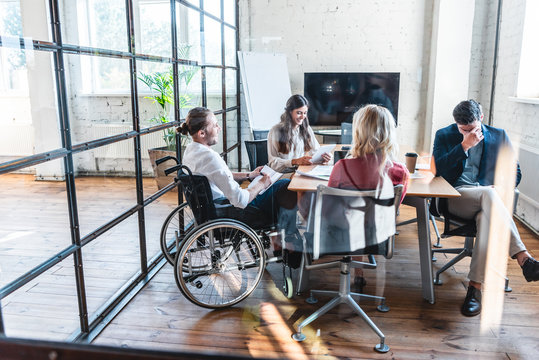 young businessman in wheelchair working with colleagues in office