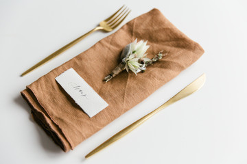 Table setting with golden colored cutlery styled with a orange linnen napkin, boutonniere and handwritten place card.