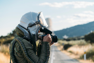 Beautiful woman using old camera dressed as an astronaut.