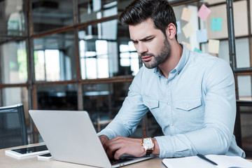 focused young businessman using laptop at workplace