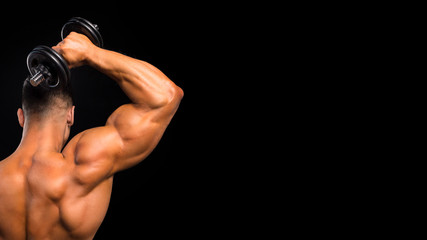 Fit muscular man uses his dumbbell to work his triceps on dark background
