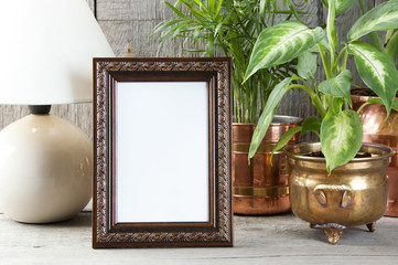 Empty brown picture frame on wooden background.