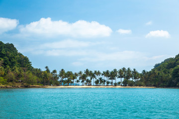 Palm trees on the sandy shore in the turquoise tropical sea against the blue sky and clouds. Beautiful seascape with a thin strip of land between the two Islands in Thailand.