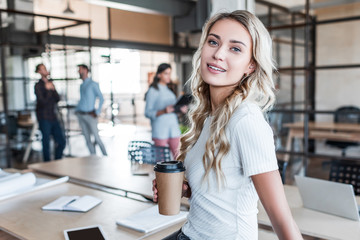 attractive young businesswoman holding paper cup and smiling at camera in office