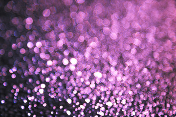 Abstract background with bokeh blurred lights. Shimmering bright red, purple, violet sequins on a dark background. The picture creates and accentuate a festive magical mood. New year, Christmas.