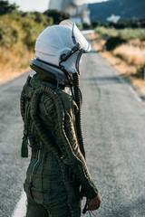 Beautiful woman walking along the road dressed as an astronaut.