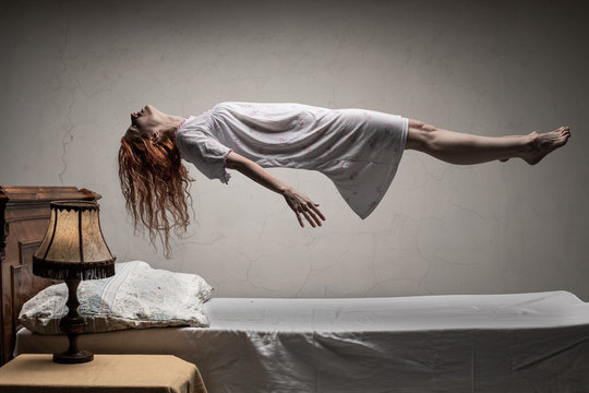 Woman levitating over bed / astral traveling, nightmare, excorcist halloween concept