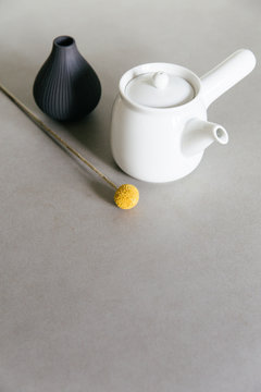Tea for one pot on a grey kitchen counter with a yellow flower and a small vase.