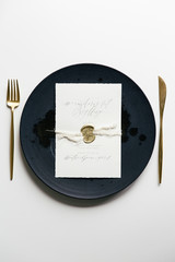 Table setting with golden colored cutlery styled with a black ceramic plate and a handwritten menu with a golden seal.