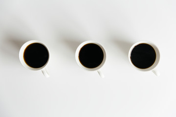 Three cups of black coffee on a white table seen from above.