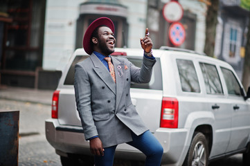 Stylish African American man model in gray jacket tie and red hat posed against silver car suv.