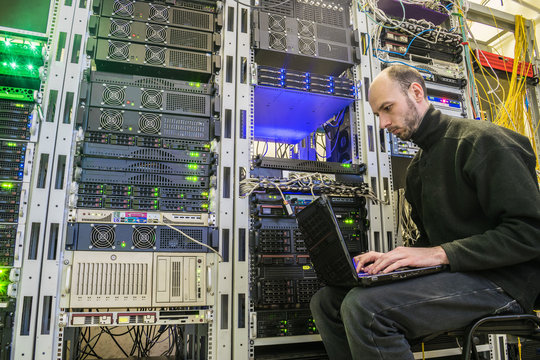 A man with a laptop sits in the server room of the data center. The system administrator works near the racks with the servers. Computer Engineer