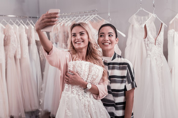 Best selfie. Positive young women smiling into the camera while taking selfie together