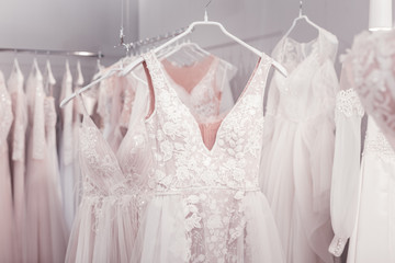 Beautiful design. Close up of a beautiful new wedding dress hanging on the hanger in the wedding boutique