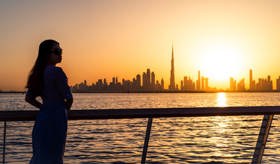 Fotobehang Kuala Lumpur Woman enjoying Dubai view at sunset