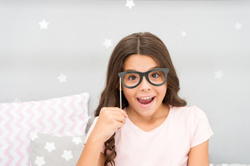 Slumber party photo booth props. Kid girl cheerful posing with vintage black eyeglasses party attribute. Prepare photo booth props hand made or buy for party. Printable photo booth props pajama party