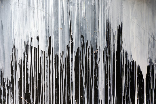 Drips of white paint on black wall.