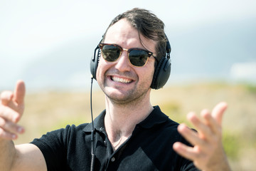 Young attractive man with sunglasses enjoying music on his headphones