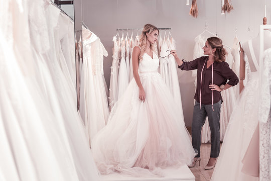 Clothes designer. Positive pleasant woman pointing at the bride while looking at the dress on her