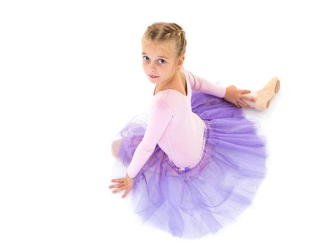 Little girl ballerina in the image posing on the floor.