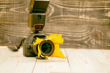 autumn yellow foliage. wooden background in retro style. camera, lens in the foliage. close-up