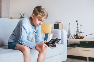 Teenager boy enthusiastically plays on the game console connected with smartphone