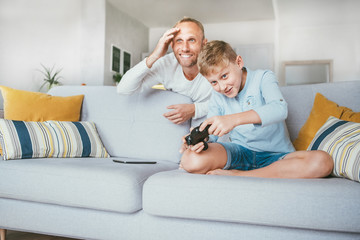 Father watching his son playing TV video game using the gamepad