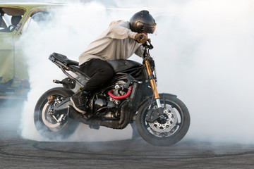 Biker burning tires and creating smoke on motorcycle in motion
