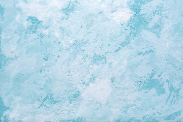 Light blue abstract background or decorative texture of old stucco wall. Textured damaged plaster. Art decor.