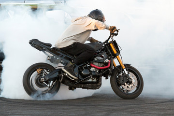 Biker burning tire and creating smoke on bike in motion