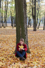 Woman with foliage near tree in park