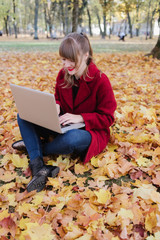 Woman with laptop sitting on ground