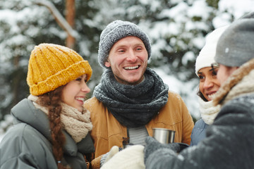 Cheerful excited young hikers in hats standing in circle and laughing while chatting together and drinking hot tea during hiking in winter forest
