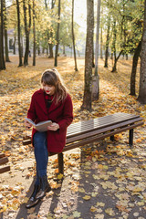 Woman reading volume on bench in park