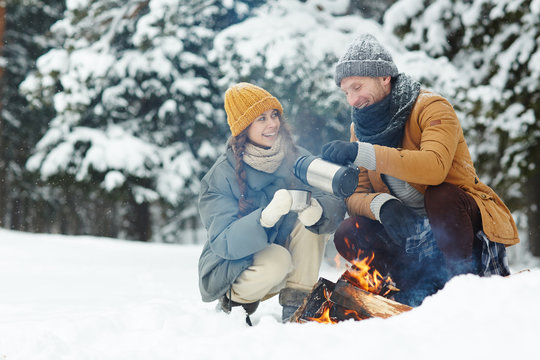 Happy excited young couple in warm jackets drinking hot tea and sitting by fire while enjoying camping in winter forest