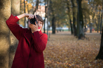 Woman with photo camera in park