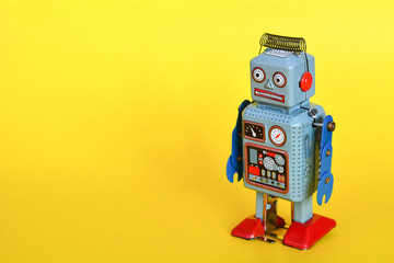Vintage tin toy robot isolated on a yellow background.